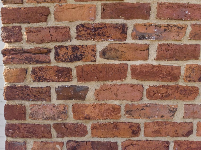 Date and initials of mason in chimney brick