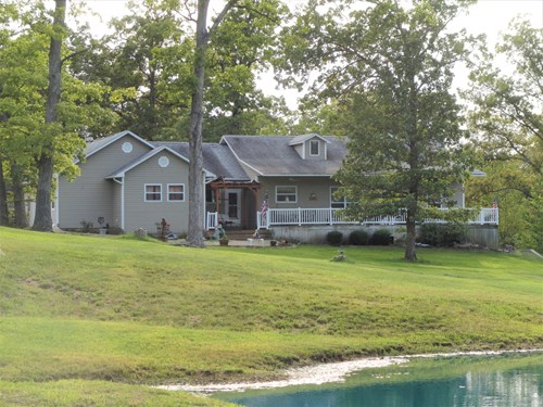 Privacy surrounds 13.84 acres Beautiuful home wtih pond
