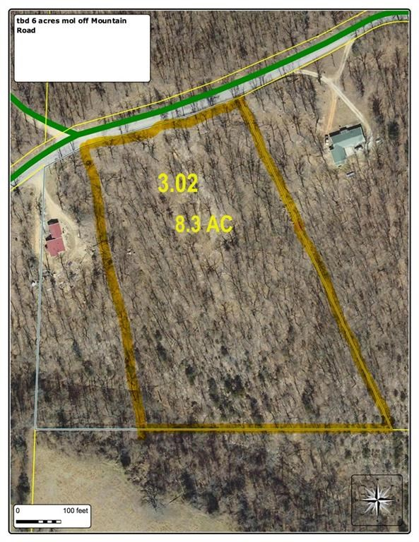 Wooded acreage with spring and rural water off paved road.
